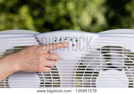 Hand selection temperature on two way window fan in home window with blurred out trees in background.