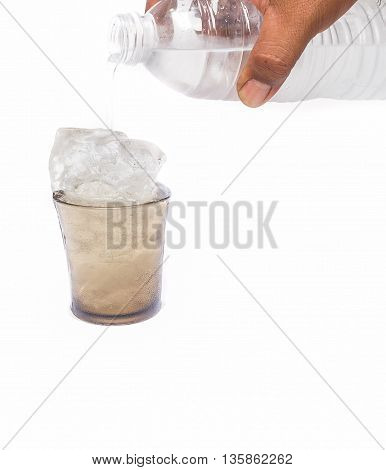 Male hand holding a bottle of Drinking water Pouring into a Glass of very cold water Drinking water thirsty.(select focus front Glass)
