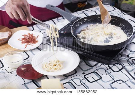 Chef putting Spaghetti carbonara to the plate with tongs / cooking spaghetti concept