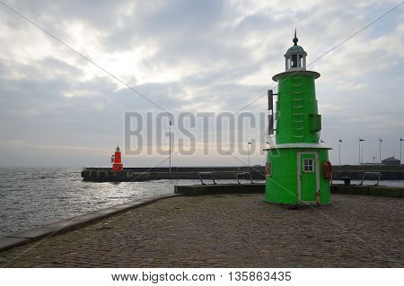 Two old lighthouse at the entrance to the port town of Helsingor, cloudy november day. Denmark