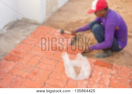worker installing cobblestone block, on road pavement, Blur blurred an image.