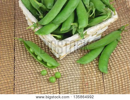 hearthy fresh green peas and pods in the basket on rustic fabric background. Summer. Vintage. Diet. Healthy eating.