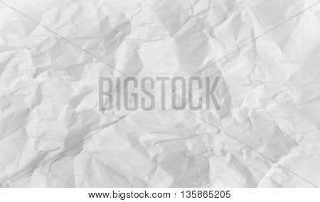 A piece of wrinkled paper on a white background. A standard-sized sheet of plain copy paper has been wrinkled extensively and then pressed flat again. The paper is completely white and appears to have been wadded up and then smoothed back to allow it to l
