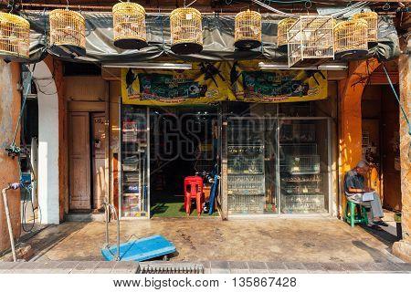 KUALA LUMPUR MALAYSIA - MARCH 17: Birds vendor sitting before his shop in Chinatown Kuala Lumpur Malaysia on March 17 2016.