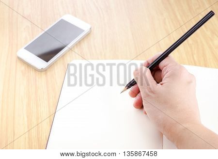 Hand Holding Black Pencil And Writing On Blank Open Notebook With Smartphone Beside It On Wooden Tab