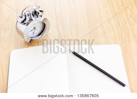 Black Pencil On Blank Open Notebook With Silver Alarm Clock Beside It On Wooden Table,template Mock