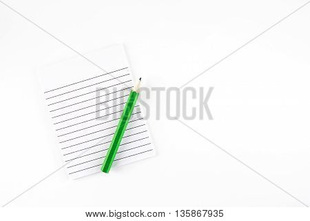 Top view of Ruled paper notepad with green pencil on white background Leave space for adding your content..