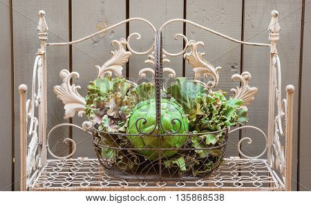 Basket with cabbages on the shelf in the background of a wooden fence