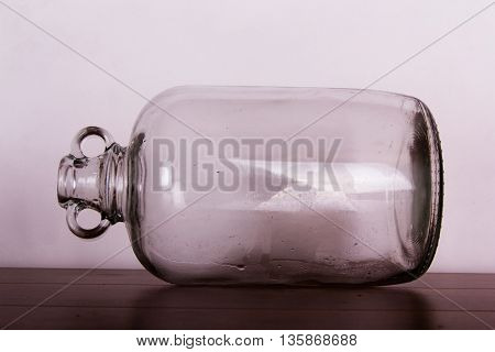 Clear Glass Demijohn Against A Light Background