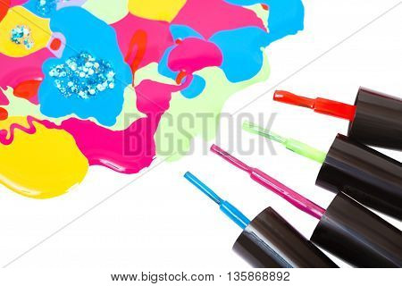 Multi-colored nail polish and brush isolated on a white background