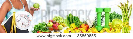 Woman hands with scales and fruits.
