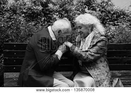Elderly couple sitting on a bench outdoors. Elderly man kisses hands of the elderly woman. Black and White. True love.