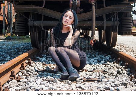 Young beautiful girl in black dress and nylons sitting on rail tracks, cargo wagons in background