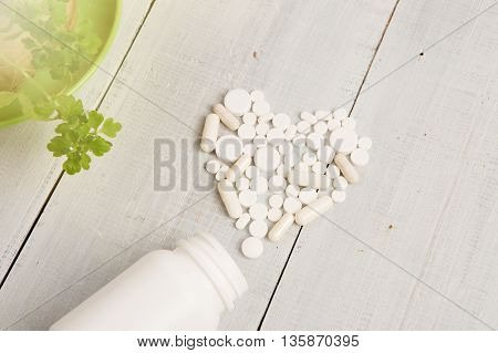 Medical Concept - White Heart Of Pills And Capsules On White Wooden Background