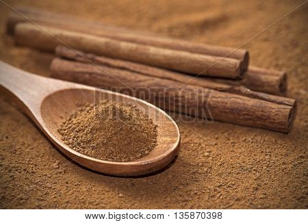 Spoon full of powdered cinnamon with cinnamon sticks