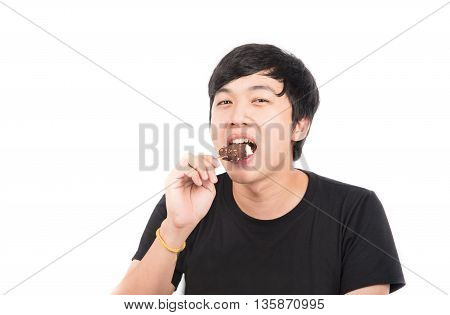 young man eating chocolate ice cream with happy face summer time