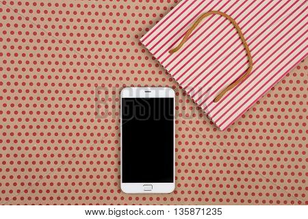 Celebratory business and technology concept - handmade striped shopping bag gift bags and white smartphone on craft paper background in red polka dots