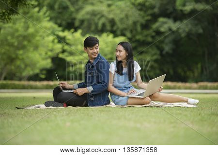 Students use the laptop in the garden.