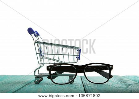 Shopping cart with reading glasses isolated on white