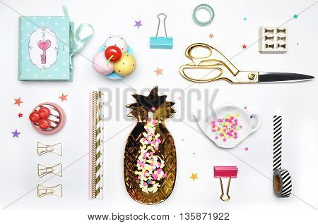 Flat lay. Accessories on the table woman desk top. View top table background mock up. Gold stationerygold pineapple mint box colorful confettis tea and strawberry.