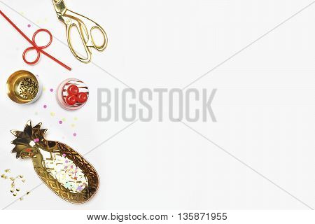 White mock up background flat lay. Gold accessories on table. View up gold items stationery. Feminine scene workspace. Gold pineapple confetti strawberry. Party background Drink and eat.