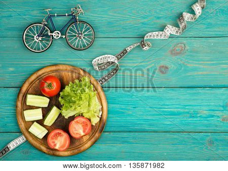 Bicycle Model, Fresh Vegetables And Centimeter Tape On Blue Wooden Desk