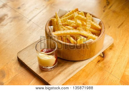 French fries in wooden bowl with Ketchup and mayonnaise