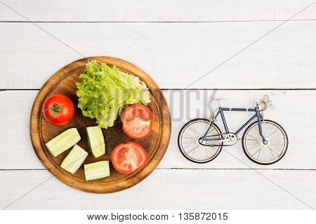 Bicycle Model And Fresh Vegetables On White Wooden Desk