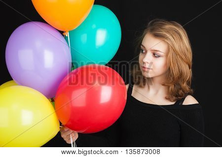 Girl With Colorful Balloons Over Black Background
