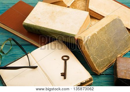 Old Key, Glasses And Stack Of Antique Books On Blue Wooden Background