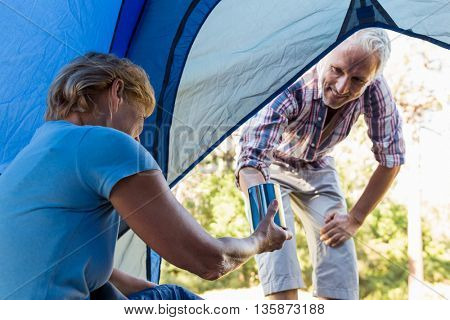 Senior couple relaxing inside their tent in the forest