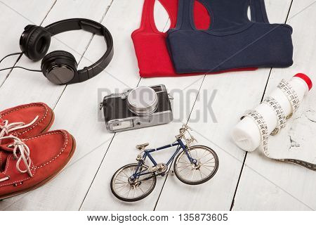 Bicycle Model, Shoes, Shirts, Headphones, Camera, Bottle Of Water And Centimeter Tape On White Woode