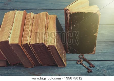 Old Keys On A Old Book And Stack Of Antique Books On Blue Wooden Background