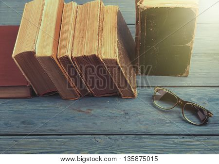 Stack Of Antique Books And Glasses On Blue Wooden Background
