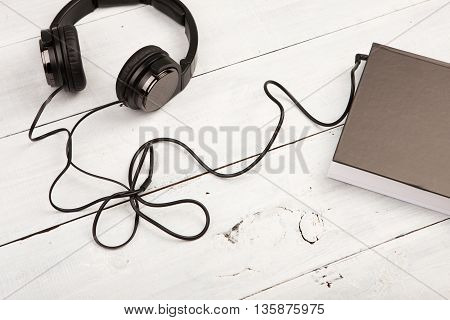 Audio Book Concept With Black Book And Headphones On White Wooden Desk