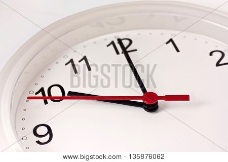 Time concept: a closeup photo of a typical white office clock on white background with copyspace