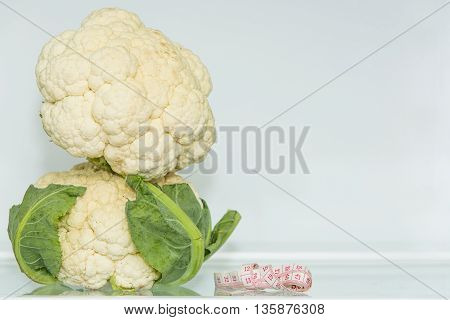 Cauliflower two(2) with measuring tape. Healthy eating. Healthy lifestyle. Diet. Source of vitamins. Vegetarian. Weight loss.
