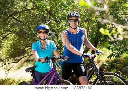 Senior couple standing with their bikes in a forest