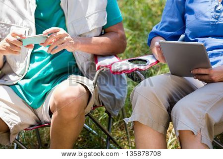 senior couple sitting with their technology object in a forest