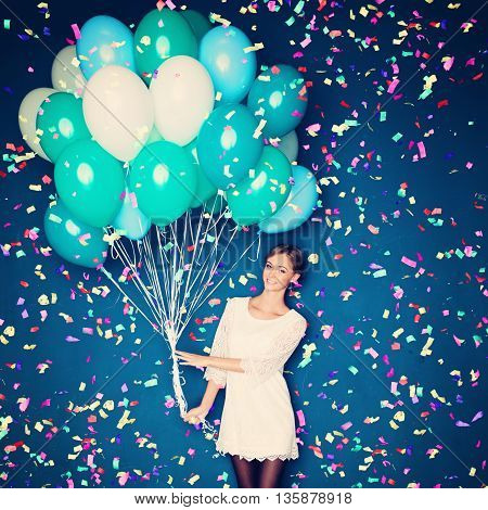 Cheerful Woman with Balloons and Confetti on Blue Background