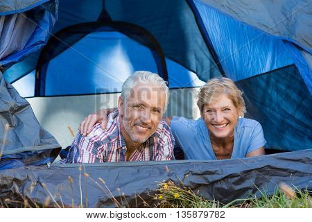 Mature couple smiling and laying on the camp site