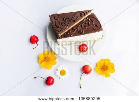 Milk souffle cakes with chocolate glaze on a plate, ripe cherries and flowers on a white tablecloth