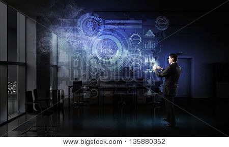 Businessman with tablet device in hands . Mixed media
