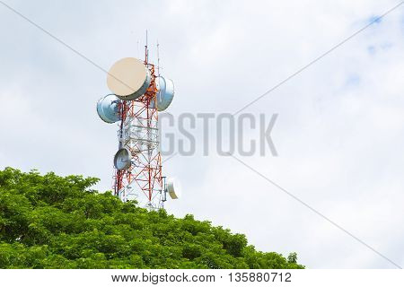 Telecommunication tower peaking above tree top on a bright sunny and full of clouds