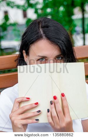 Woman is reading book. Girl with book in white polo black pant and red shoes is sitting on bench in the park is learning studying. Woman holding book in front of her face. hide behind a book