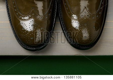 Green lacquered oxford shoes wooden background. Top view. Close up.