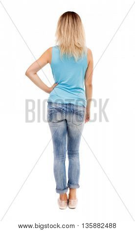 back view of standing young beautiful  woman.  girl  watching. Rear view people collection. girl in jeans and a blue t-shirt is resting his right hand in the waistband