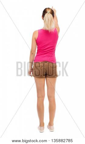 Back view of  pointing woman. beautiful girl. Rear view people collection.  backside view of person.  Isolated over white background. Blonde in brown shorts shows up with his left hand.