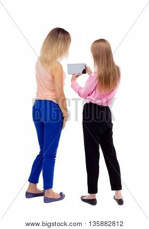 Back view two young woman look at smart phone. Rear view people collection.  backside view of person. Rear view. Isolated over white background. Two blonde girls looking at something in the tablet PC.