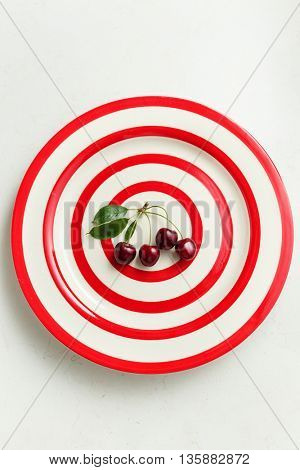 Dark red summer cherries on plate
